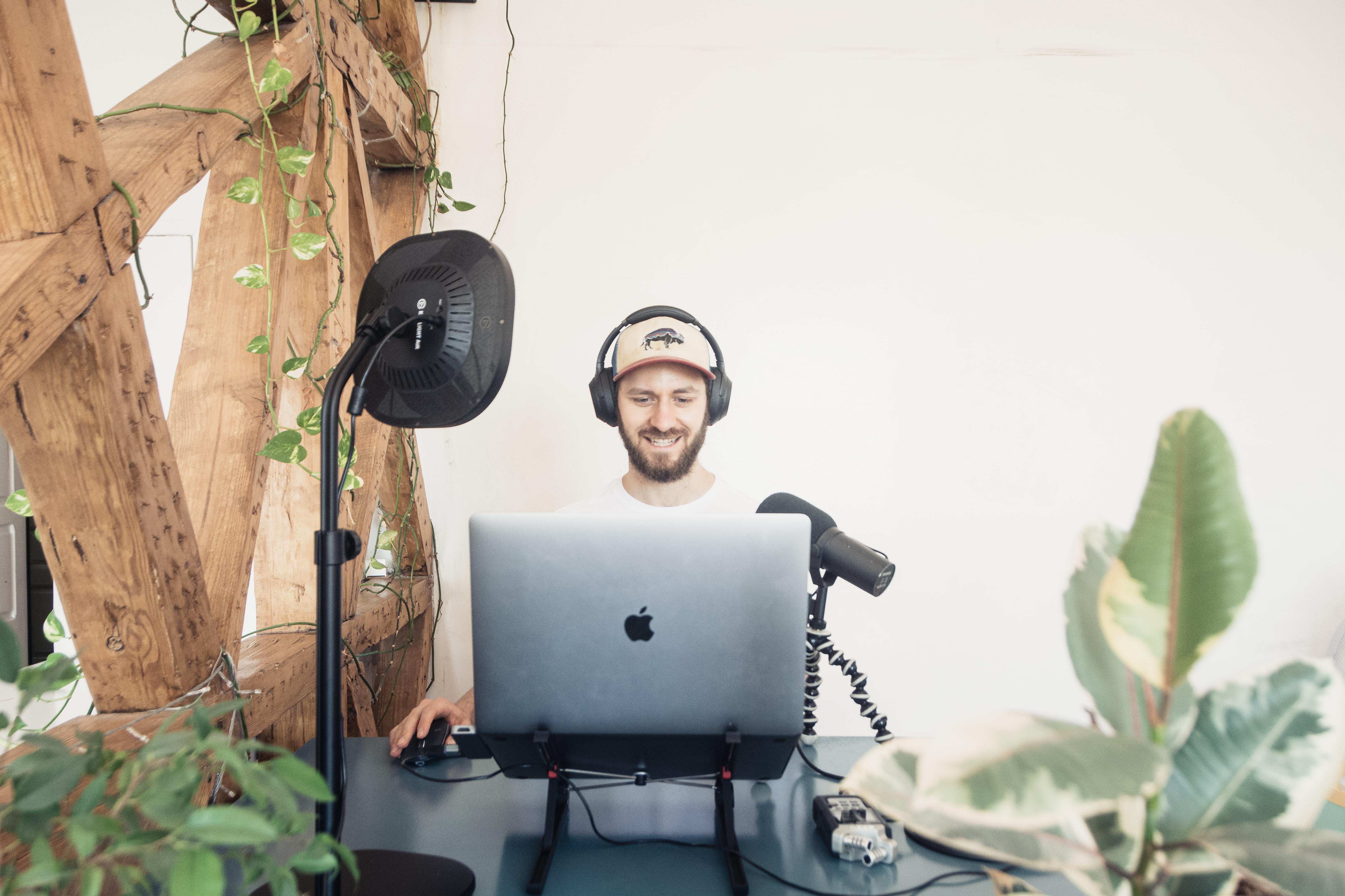 man-at-desk-with-mic-headphones-light-computer